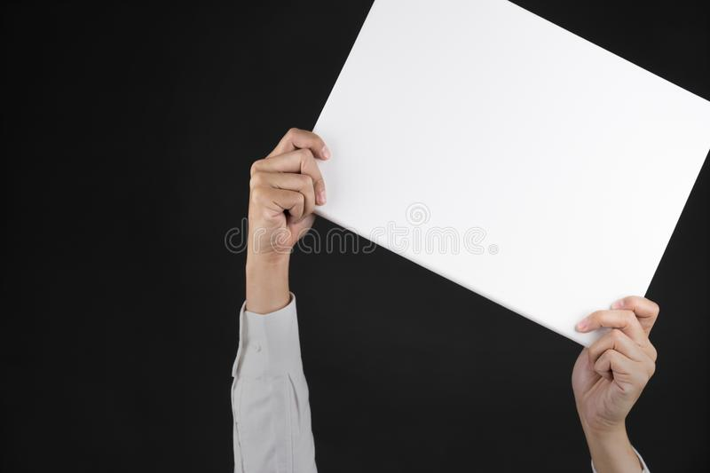 Businessman holding blank white board in his hand with black background.clipping path,copy space royalty free stock image