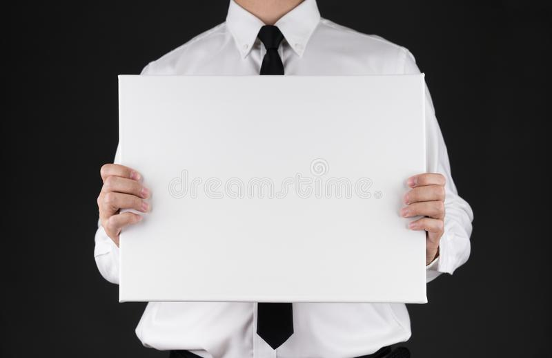 Businessman holding blank white board in his hand with black background.clipping path,copy space royalty free stock images