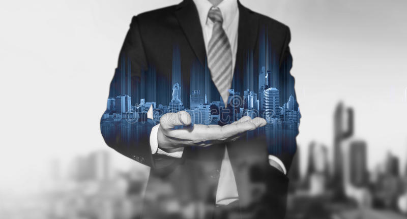 Businessman holding blue modern buildings hologram on hand, with black and white city background. S royalty free stock images