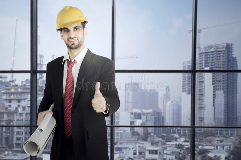 Businessman holding blueprints and showing thumb up royalty free stock image