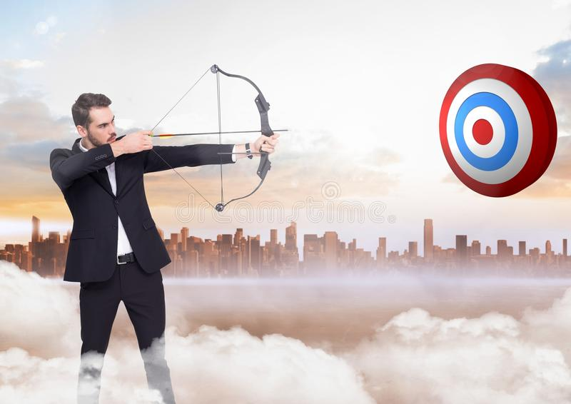 Businessman holding bow and arrow while aiming at the target board stock images