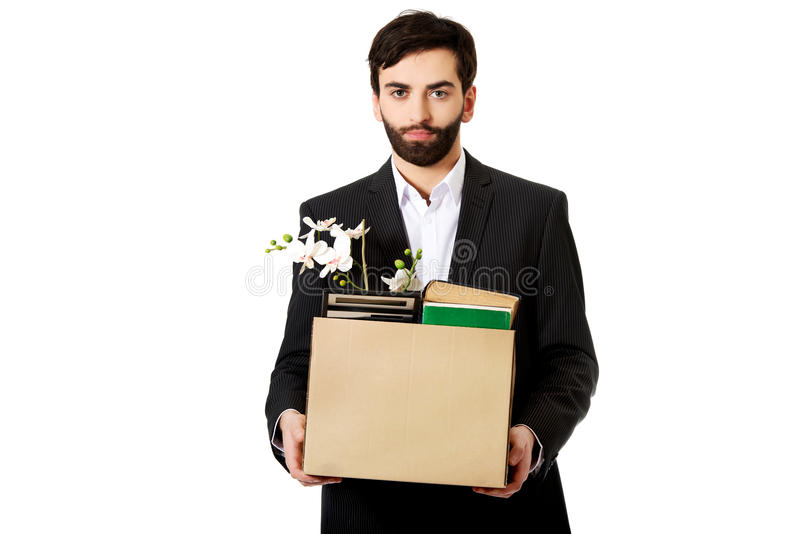 Businessman holding box with personal belongings. Fired businessman holding box with personal belongings stock photography