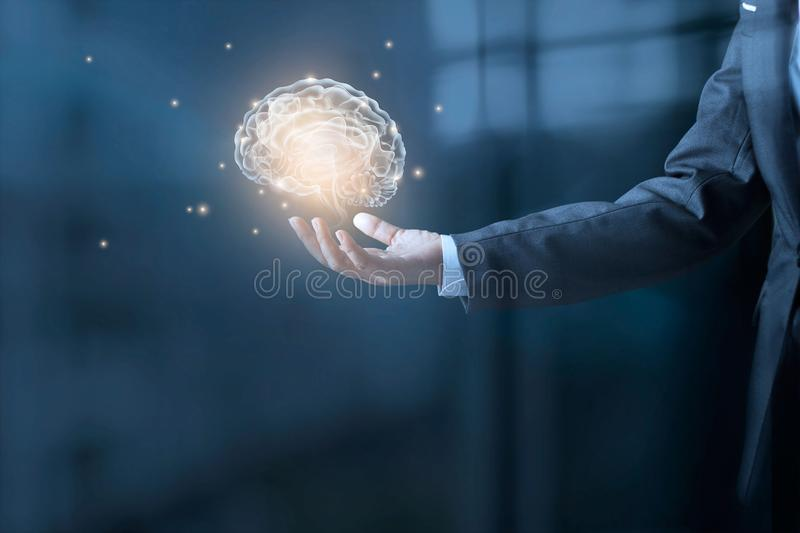 Businessman holding a brain and stardust in hand. On blue office background royalty free stock image