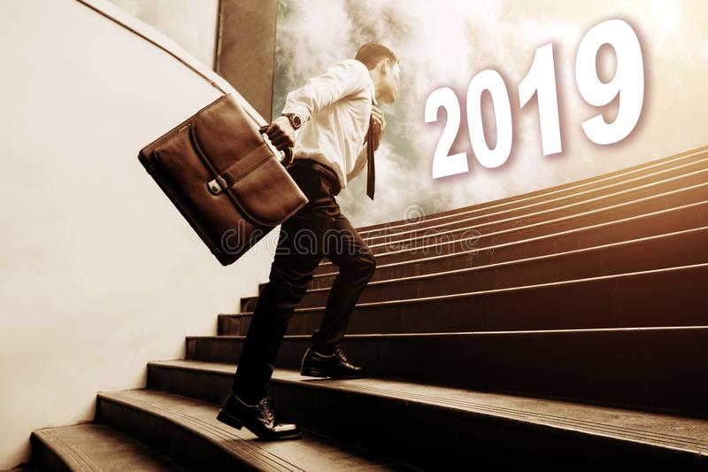 businessman holding briefcase and walking on staircase and looking to future 2019 newyear concept. royalty free stock photography