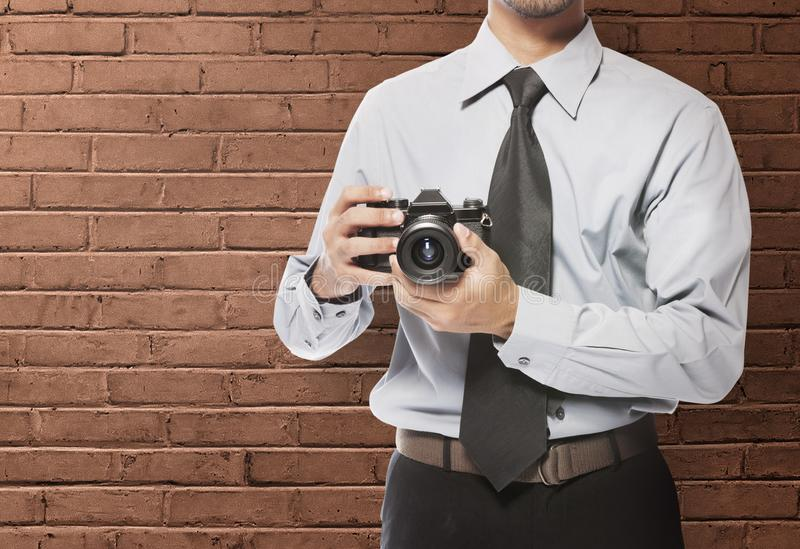 Businessman holding the camera on his hand standing stock photos