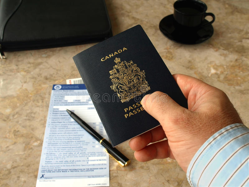 Businessman holding Canadian passport. On U.S. customs and border form background stock photo