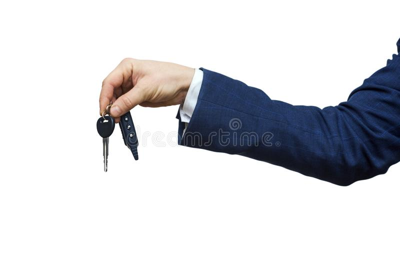 Businessman holding the car key, isolated on white background. Businessman offering a car key. Close-up of driver`s hand showing stock images