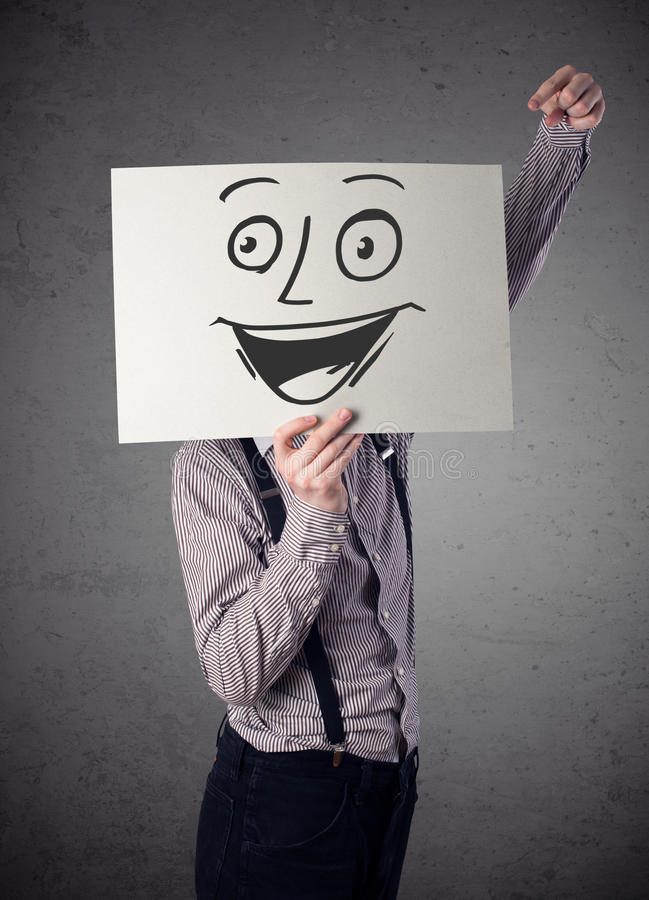 Businessman holding a cardboard with smiley face on it in front. Young businessman holding a cardboard with a smiley face on it in front of his head royalty free stock image