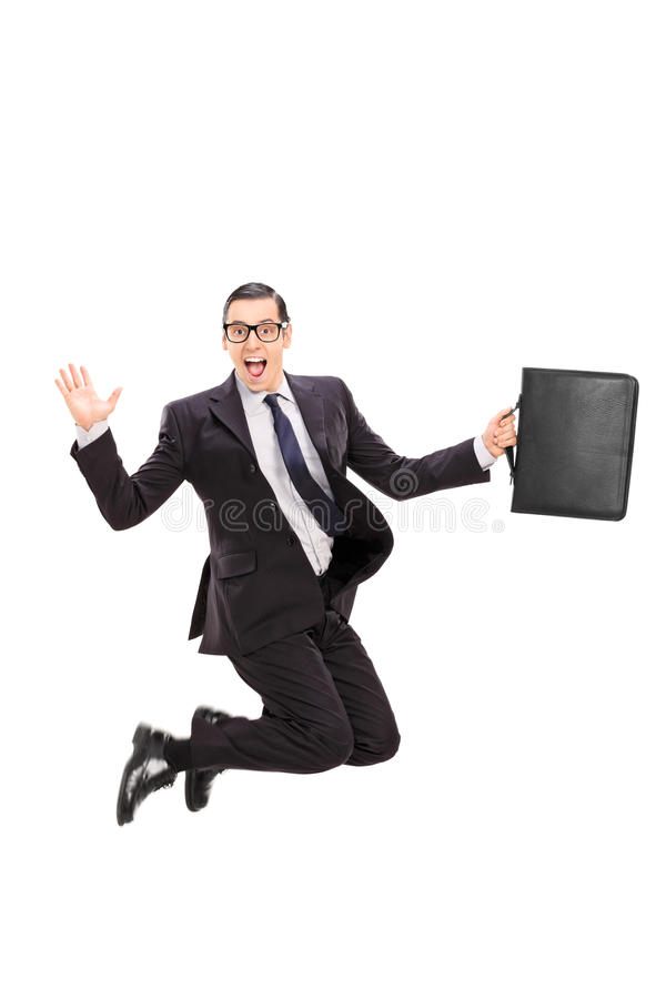 Businessman holding a case and jumping in the air royalty free stock images