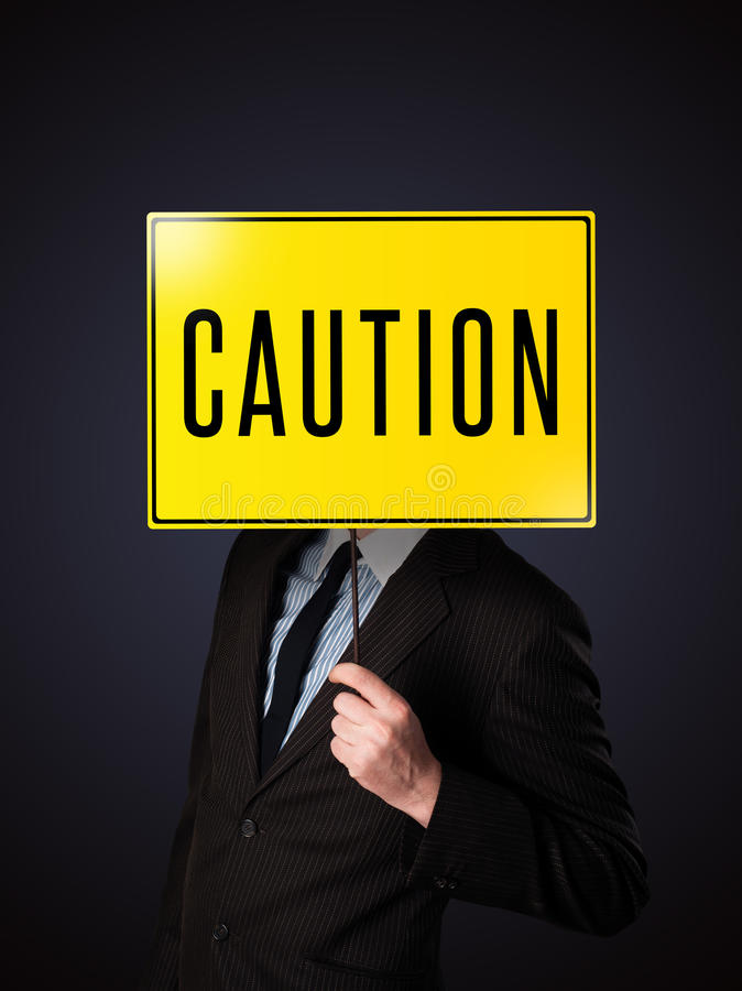 Businessman Holding A Caution Sign Stock Photo