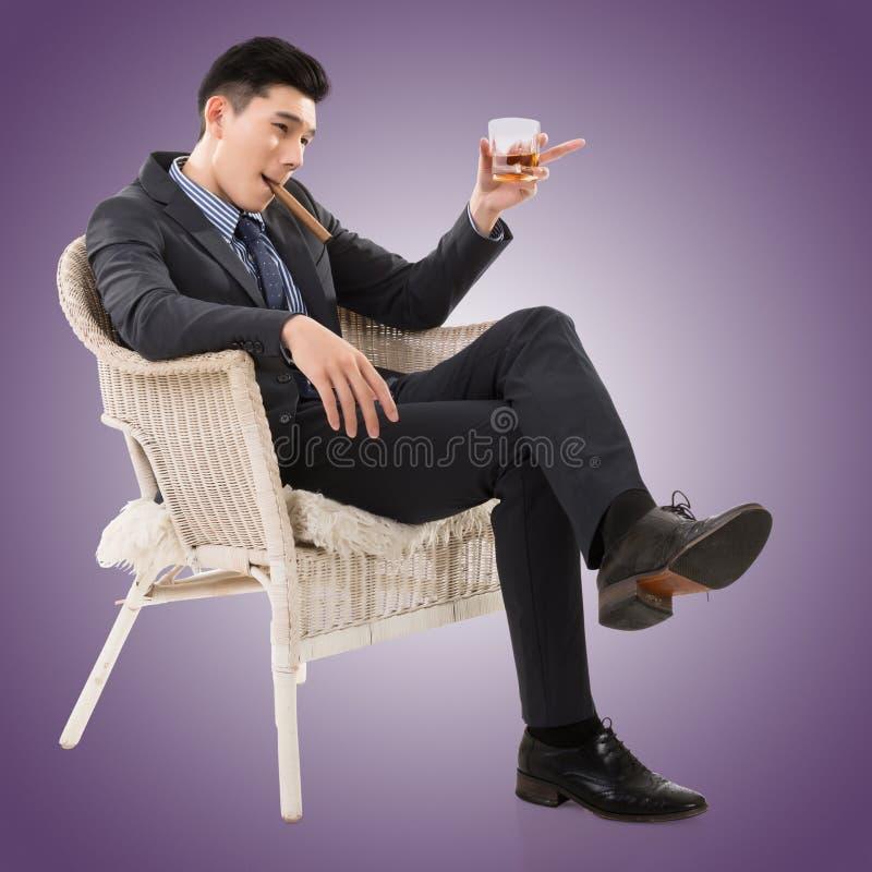 Businessman holding a cigar royalty free stock photos