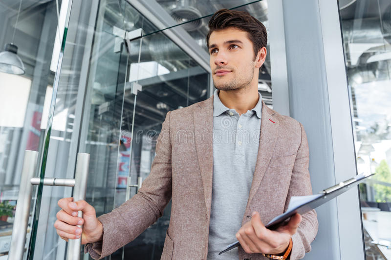 Businessman holding clipboard and entering the door in office. Attractive young businessman holding clipboard and entering the door in office stock photography