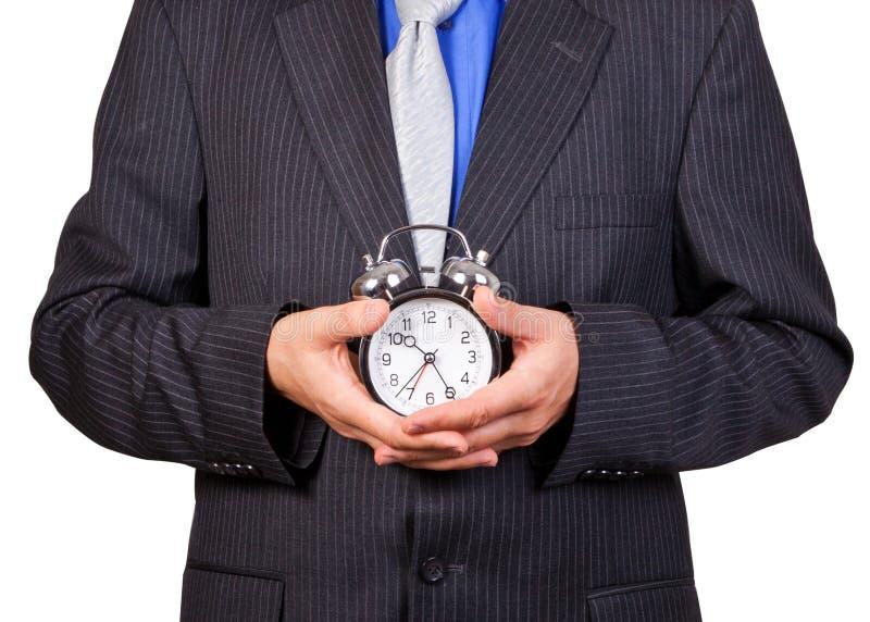 Businessman holding a clock stock image