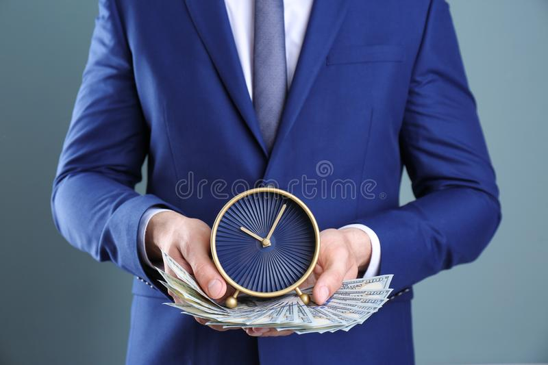 Businessman holding clock and money on color background. Time management stock image