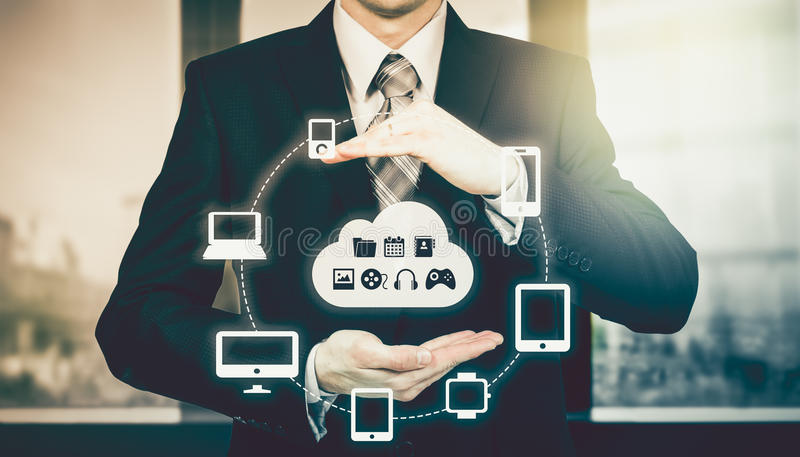 Businessman holding a cloud connected to many objects on virtual screen concept about the internet of things. Businessman holding a cloud connected to many royalty free stock image