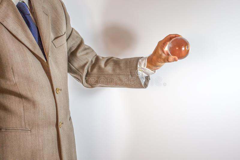Businessman holding a crystal ball. Isolated on white background stock image