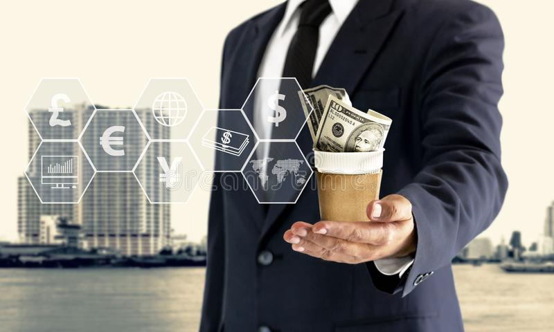 Businessman holding a cup, put a dollar in the hand and a virtual icon royalty free stock photo