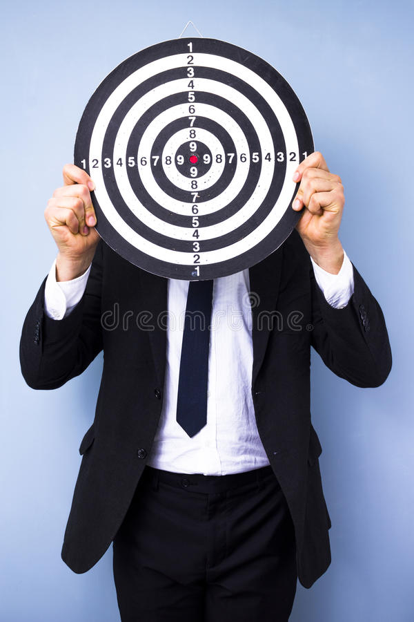 Businessman holding dartboard. In front of his face stock images