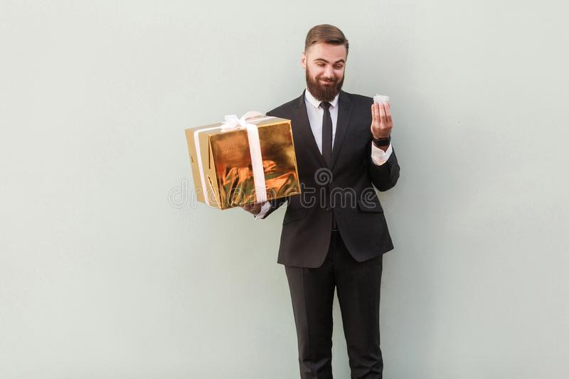 Choise concept. Businessman holding different boxes. Studio shot. Businessman holding different boxes. Looks with a sneer at a small box. Studio shot stock photo