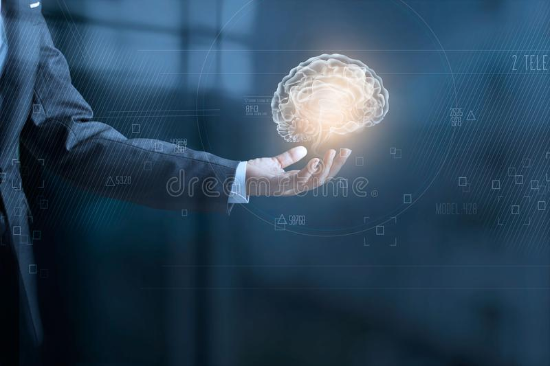 Businessman holding digital human brain and icon graphic. In hand on dark blue background royalty free stock images