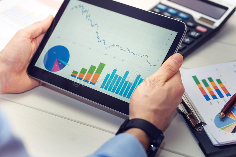 Businessman holding digital tablet with graphs and charts report royalty free stock photo