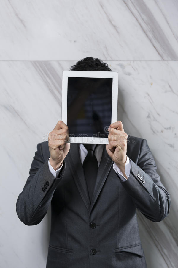 Businessman Holding A Digital Tablet Up Over His Face. Royalty Free Stock Images