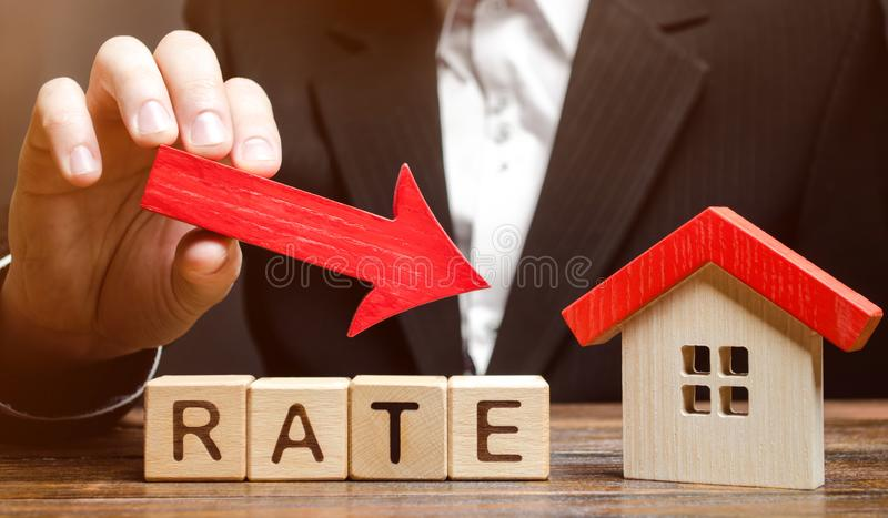 Businessman holding the down arrow on wooden blocks with the word Rate and house. Low interest in mortgages. Reducing interest. Payments for mortgage. The fall royalty free stock images