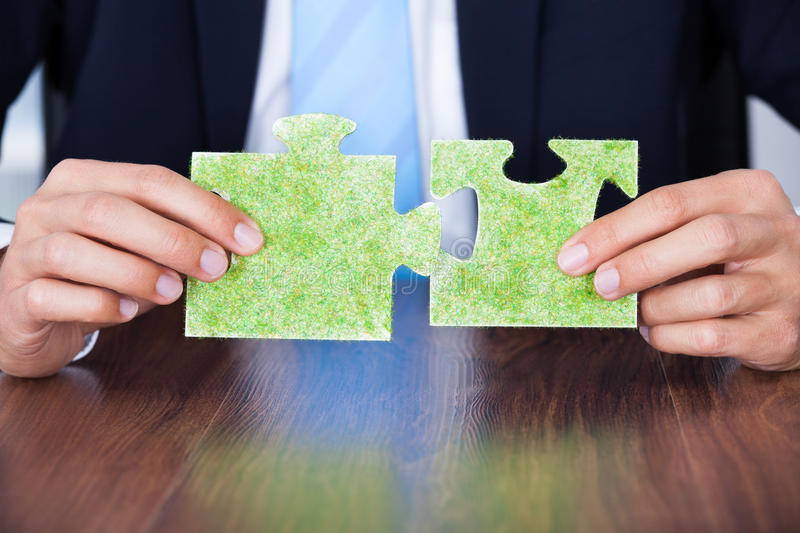 Businessman holding eco friendly jigsaw puzzle. Close-up Of Businessman Holding Eco Friendly Jigsaw Puzzle stock photo