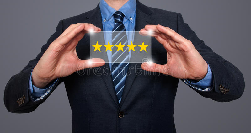 Businessman holding five star rating royalty free stock image
