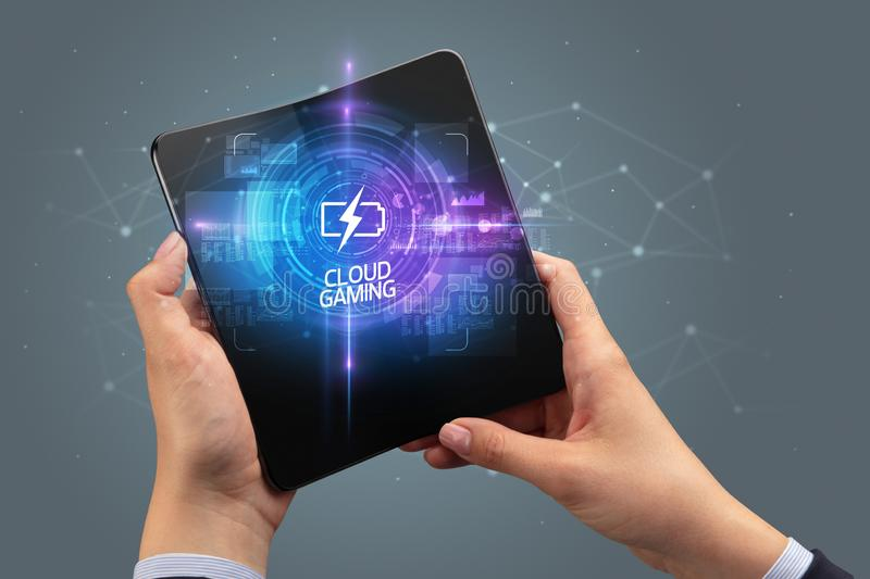 Businessman holding a foldable smartphone, technology concept. Businessman holding a foldable smartphone with FUTURISTIC inscription, new technology concept stock photo