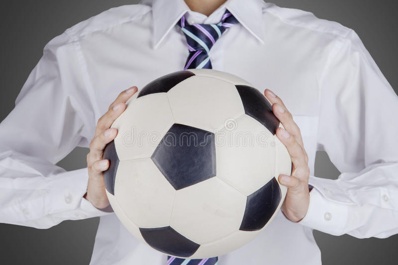 Businessman holding a football stock photography