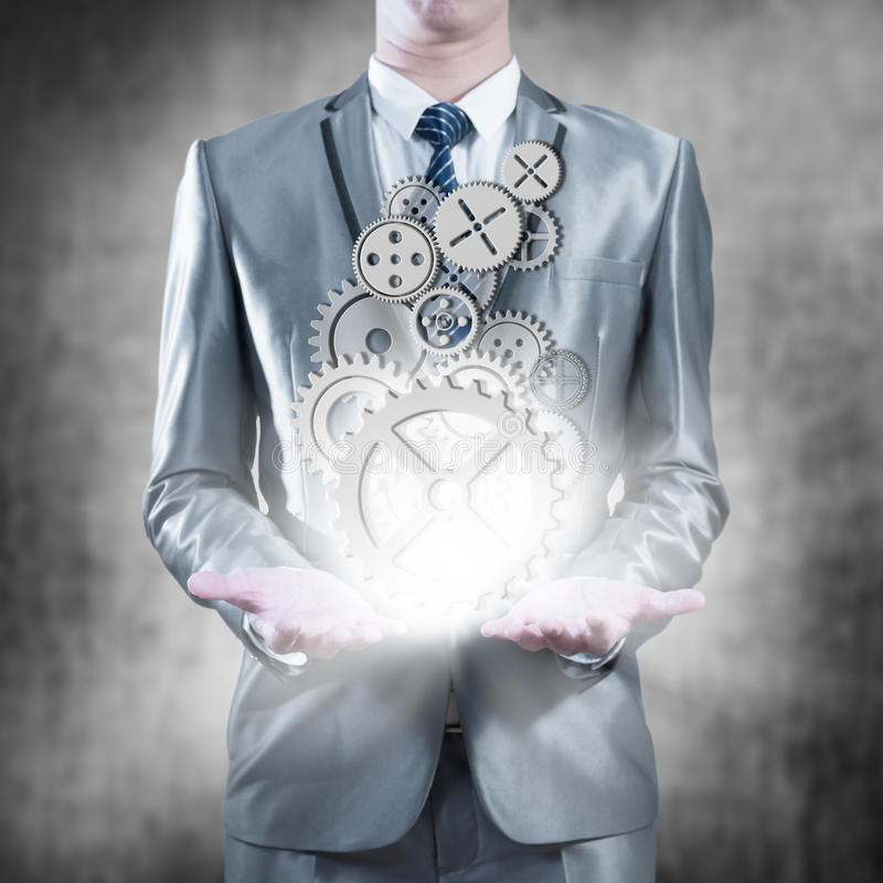 Businessman holding gears in palms, business strategy concept royalty free stock photo