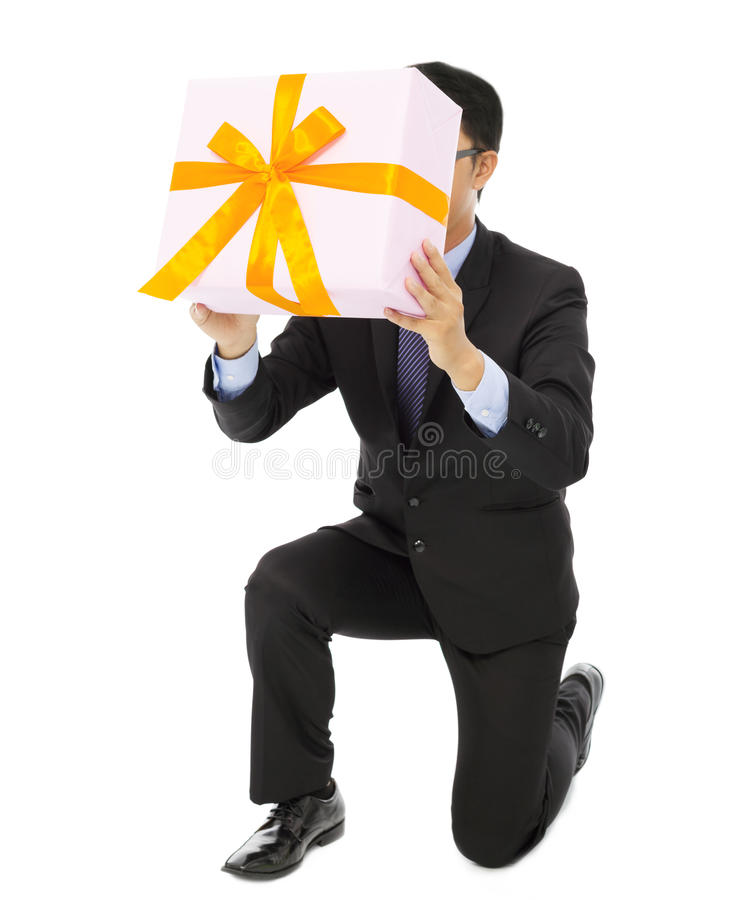 Businessman holding a gift box and kneel. Isolated on white background royalty free stock photo