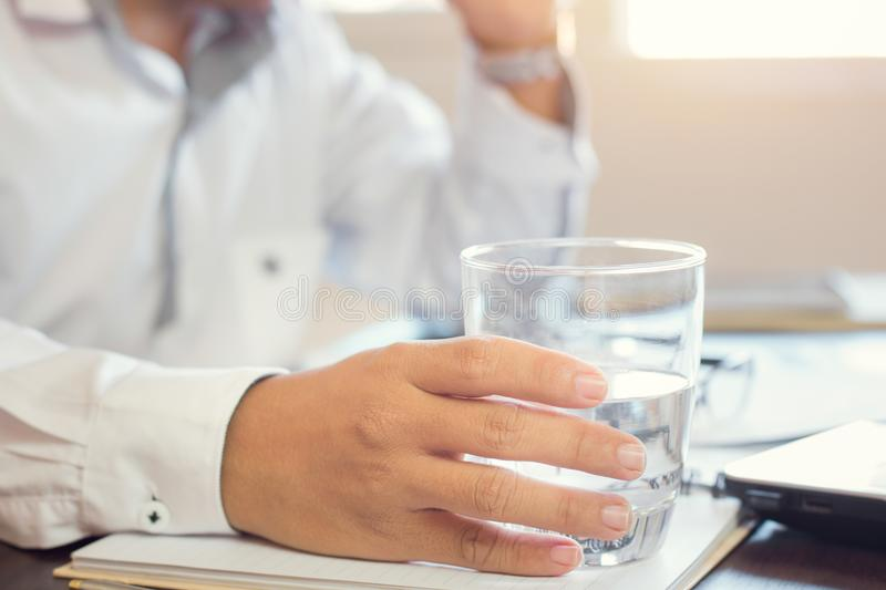 Businessman holding glass of drinking water royalty free stock image