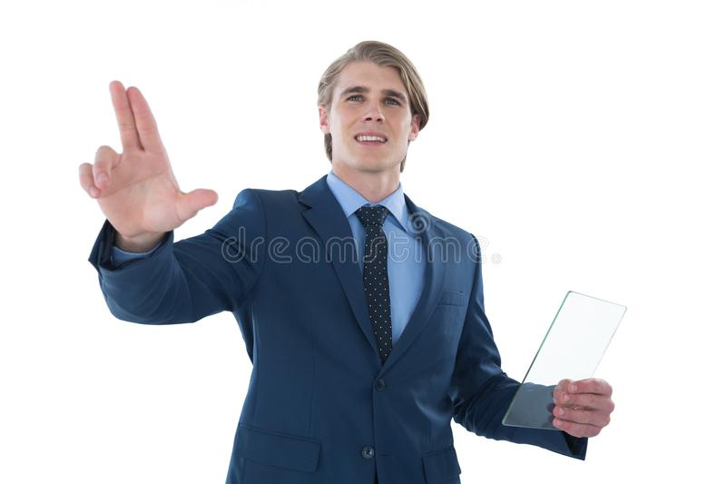 Businessman holding glass interface while touching imaginary screen. Against white background royalty free stock photo