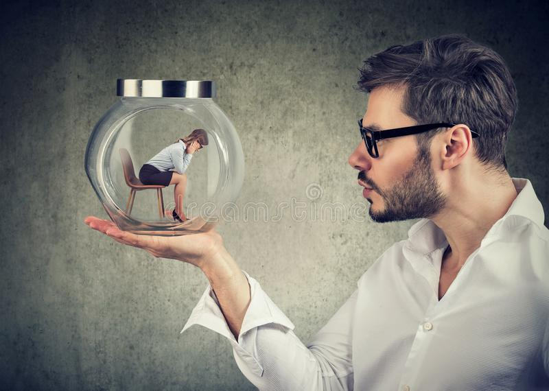 Business man holding a glass jar with a young sad business woman trapped in it. Businessman holding a glass jar with a young sad businesswoman trapped in it royalty free stock image