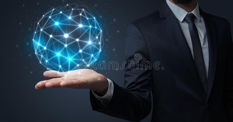 Businessman holding global connection concept. Businessman in suit holding global connection symbol on his hand stock photo
