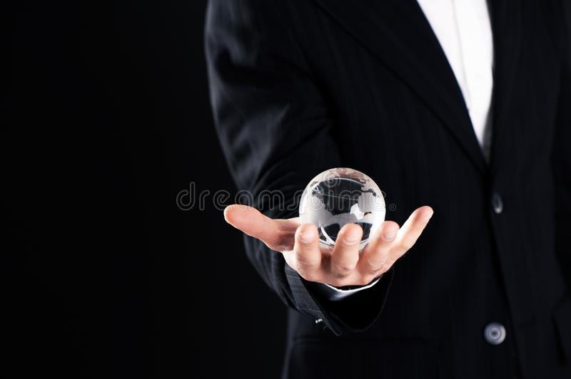 Businessman holding globe in a dark black background. Close up stock photography