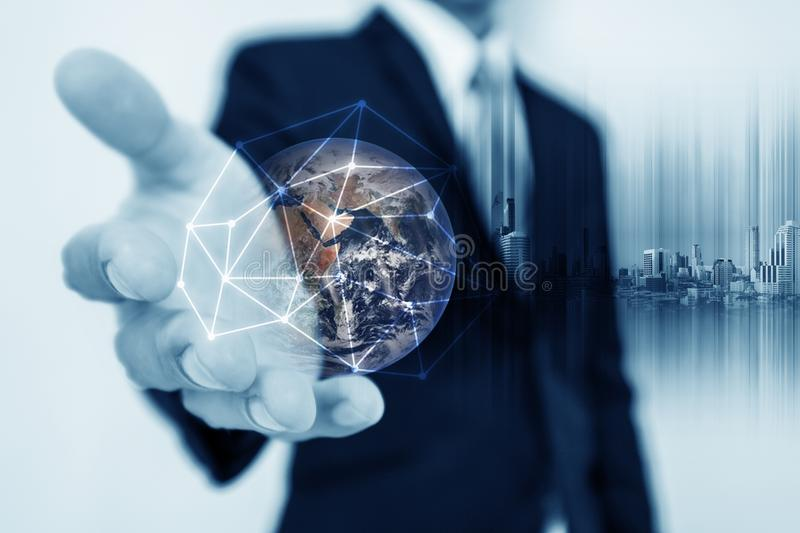 Businessman holding globe hologram with network connection lines. Global business networking, currency exchange and travel around stock photo