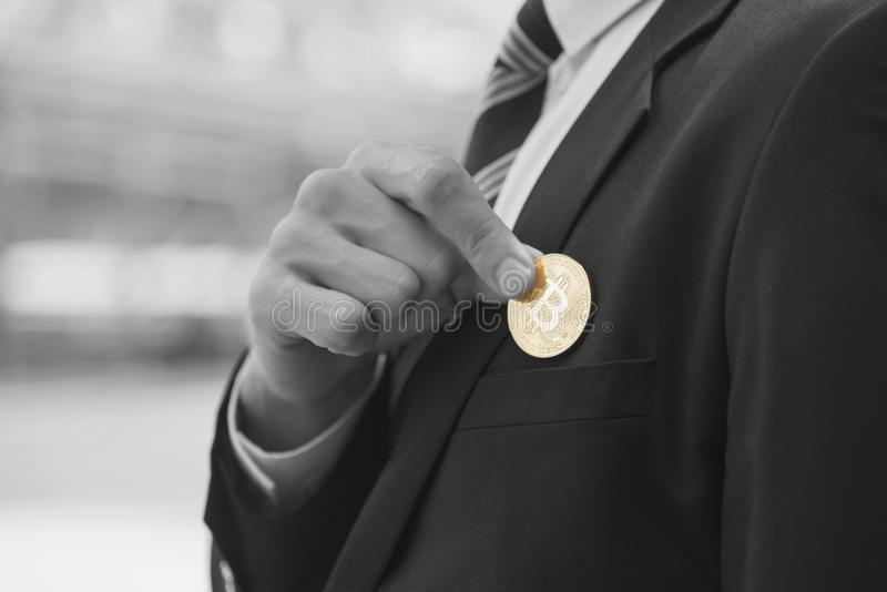 Businessman holding gold bitcoin from suit pocket.  royalty free stock photos