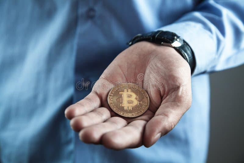 Businessman holding golden bitcoin. Virtual money concept stock photography