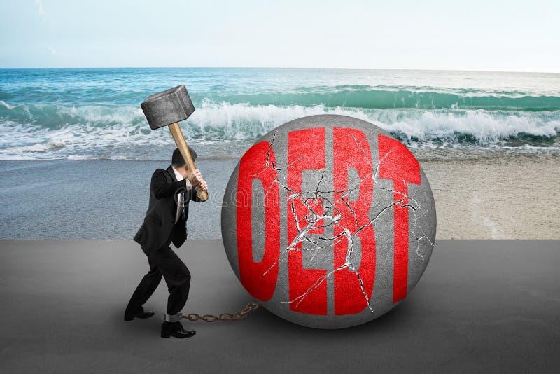 Businessman holding hammer hitting cracked DEBT ball with sea be. Businessman holding hammer hitting cracked DEBT ball with nature sea beach background royalty free stock images