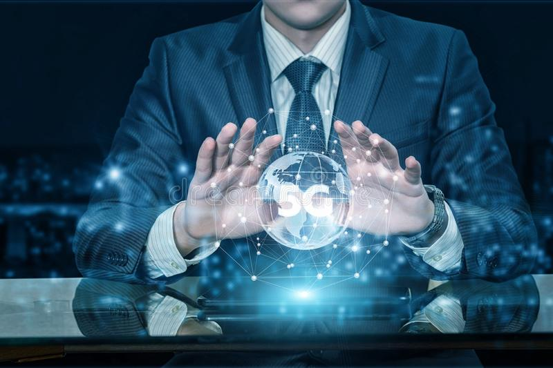 A businessman holding hands above a globe with 5G symbol inside royalty free stock photography