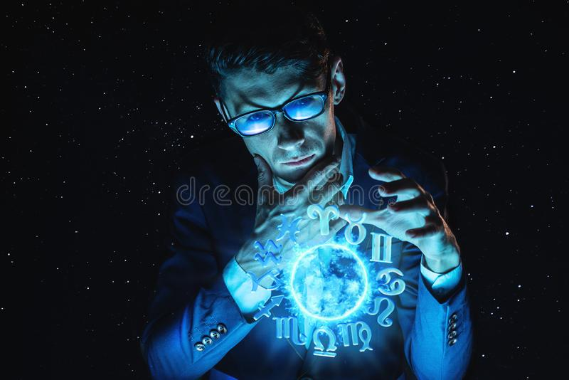 Businessman holding hands over the magic sphere with a horoscope to predict the future. Astrology as a business stock photography