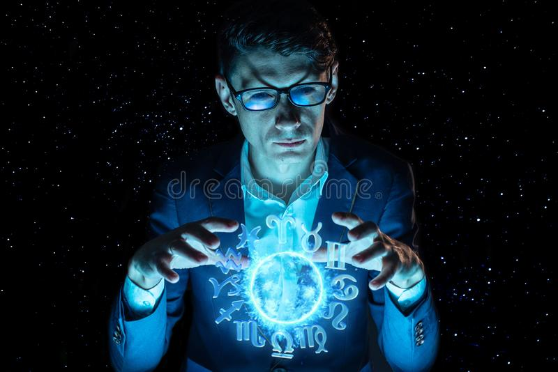 Businessman holding hands over the magic sphere with a horoscope to predict the future. Astrology as a business royalty free stock photo