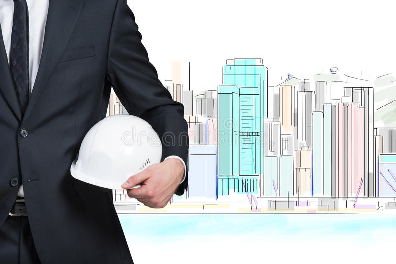 Businessman holding helmet. On drawing skyscraper background royalty free stock photos