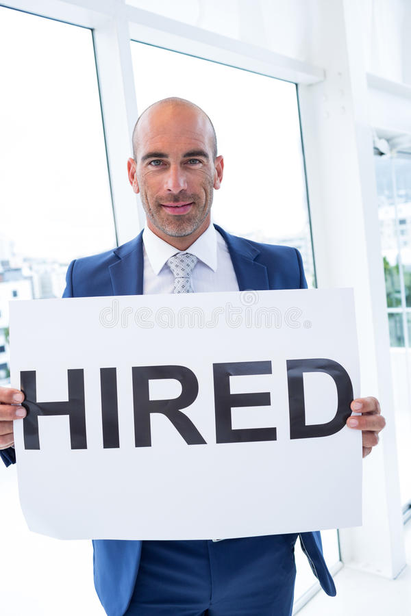 Businessman holding a hired sign. In the office stock photos