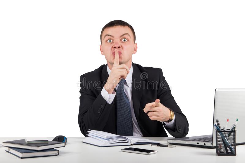 Businessman holding his finger in front of his mouth and making silence gesture shh stock photo