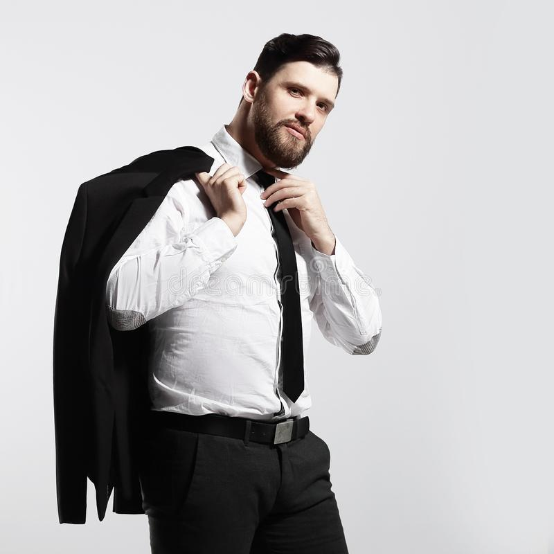 Businessman holding his jacket over his shoulder and straightens his tie royalty free stock image