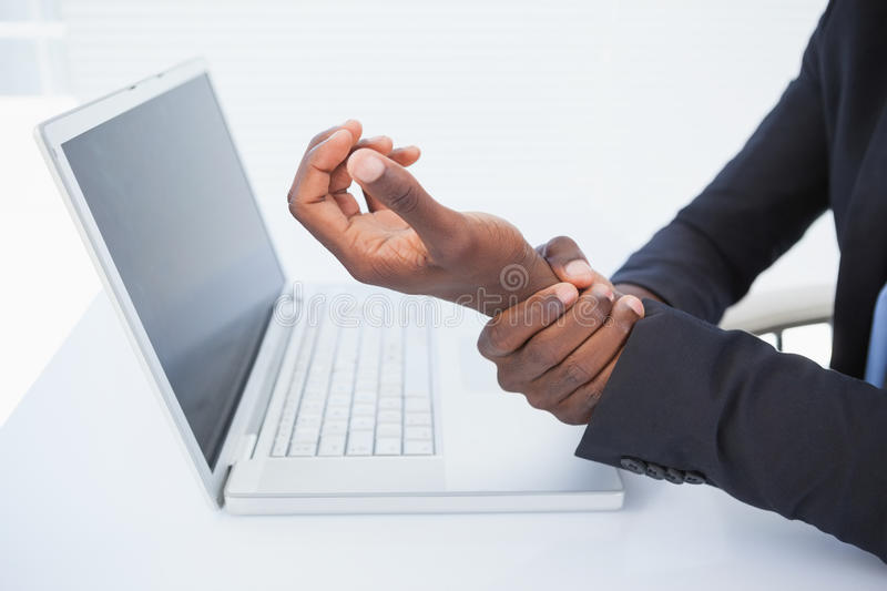 Businessman holding his sore wrist from typing stock images